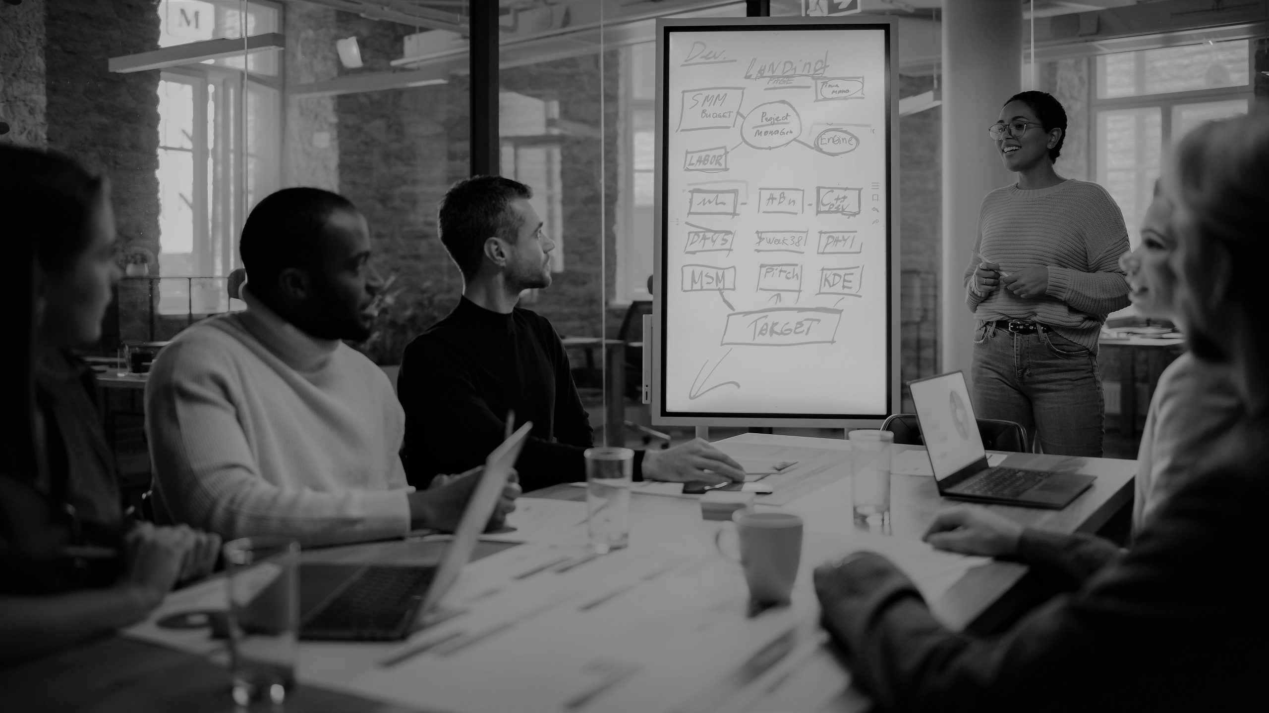 Project Manager Makes a Presentation for a Young Diverse Creative Team in Meeting Room in an Agency. Colleagues Sit Behind Conference Table and Discuss Business Development, User Interface and Design